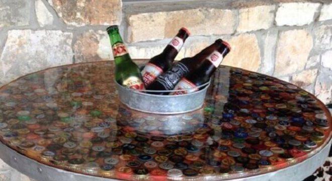 Mesa de carretel com base feita de tampas de garrafas