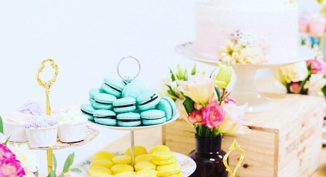 mesa de guloseimas decorada com arranjo de flores e macarons coloridos