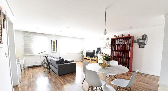 Mesa redonda branca com 4 cadeiras Eames em sala integrada Projeto de Carla Cuono