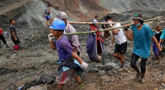 Voluntários resgatam uma das 162 vítimas do deslizamento na mina de jade