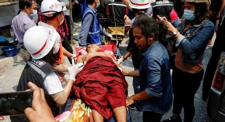 Paramédicos socorrem um monge ferido durante repressão a um  protesto em Mandalay