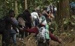 Nos trechos mais difíceis o grupo dá as mãos, formando um imenso cordão humano que se estica e se encolhe ao ritmo dos acidentes do terreno. Os mais pesados e os mais velhos se apoiam em gravetos que afundam na lama