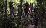 Os haitianos caminharão dois dias inteiros pela selva até o topo de uma montanha na fronteira com o Panamá. Os guias lideram a marcha.Cada migrante pagou 300 dólares pelo acompanhamento.Uma pessoa em boas condições físicas poderia fazer o trajeto em um único dia,