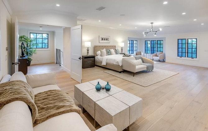 Esta é a suíte principal da mansão, que tem dois sofás, poltronas e mesas de centro, além é claro da cama