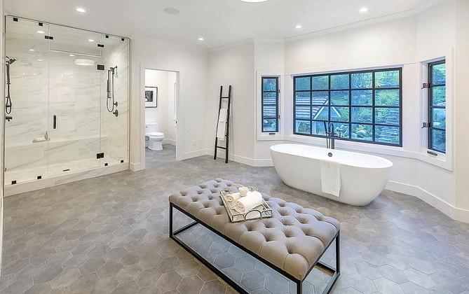 O banheiro principal da mansão impressiona pelo tamanho e conta tanto com chuveiro quanto com banheira, além de uma enorme janela com vista para a natureza