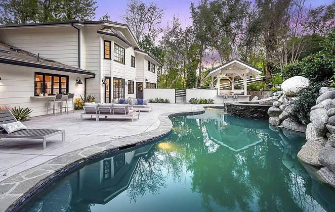 A área total da propriedade é de aproximadamente 4,775 mil m², com uma piscina deslumbrante no estilo lagoa
