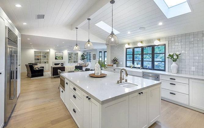A cozinha foi construída com uma grande ilha e já vem com todos os eletrodomésticos de uma famosa marca