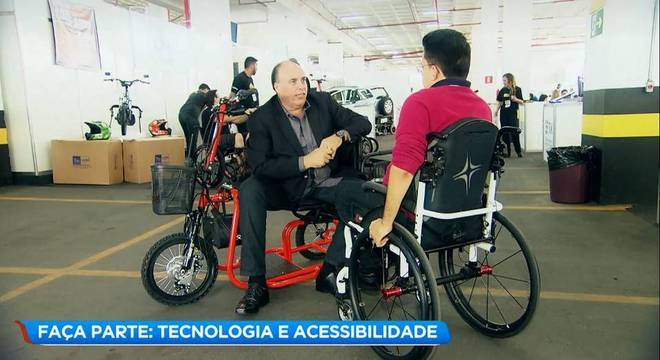 Thiago Helton, no meio da feira, conversando com Rodrigo Rosso (Presidente da ABRIDEF) que está sentado em um triciclo.