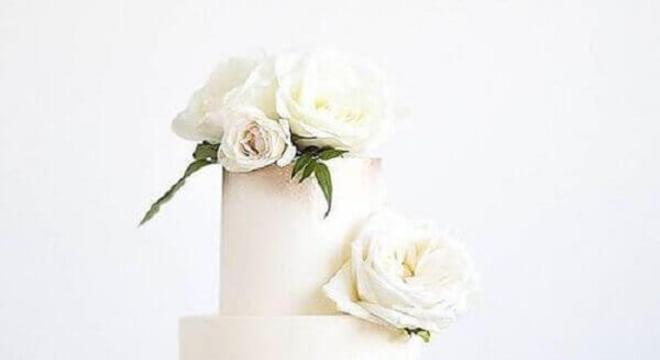 modelo moderno de bolo de casamento com acabamento dourado e rosas brancas