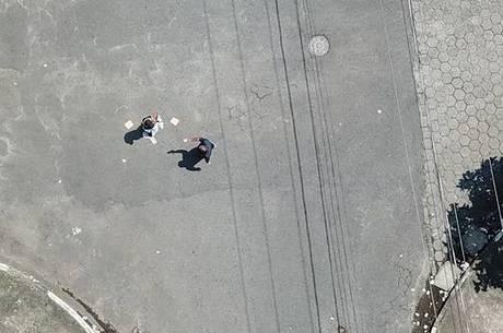 Momento em que homem distribui santinhos em São Vicente (SP)