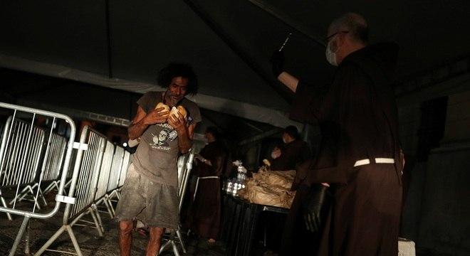Morador em situação de rua recebe pães em ajuda humanitária em São Paulo