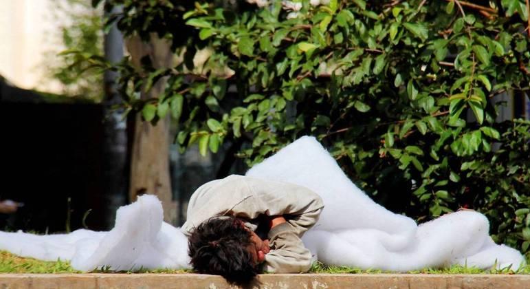 Morador de rua dorme enrolado em cobertor com a chegado da estação fria na cidade de São Paulo