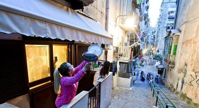 Moradora canta e bate panela na varanda de seu apartamento em Nápoles