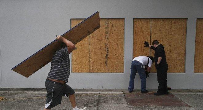 Moradores colocam madeira compensada para proteger construções em Port St. Joe, na Flórida