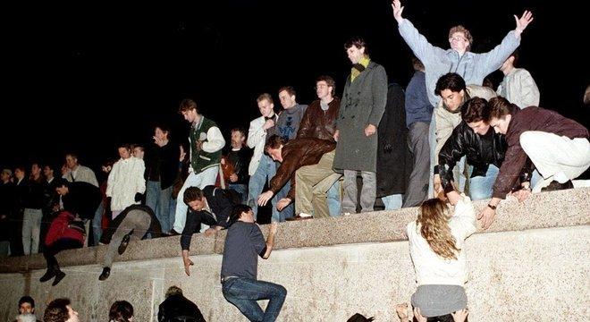 Moradores de Berlim Oriental escalaram o Muro em 9 de novembro de 1989, derrubando a Cortina de Ferro na Alemanha