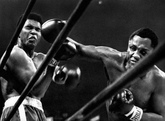 Na foto, Cassius Clay, ou melhor, Muhammad Ali, ou melhor, o Rei do Boxe está à esquerda e, à direita, Joe Frazier, disputando o campeonato mundial dos pesos pesados em pleno Madison Square Garden, em Nova York, no ano de 1971