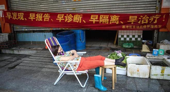 Mulher descansa com máscara na província de Guangzhou, na China