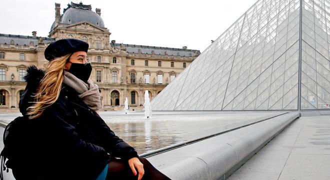 mulher de máscara em frente ao louvre em paris
