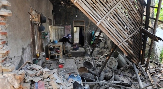 Mulher é vista dentro de casa destruída pelo terremoto