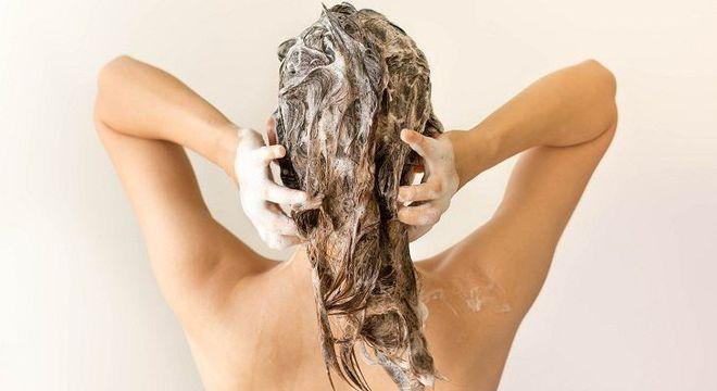 mulher lavando o cabelo com shampoo