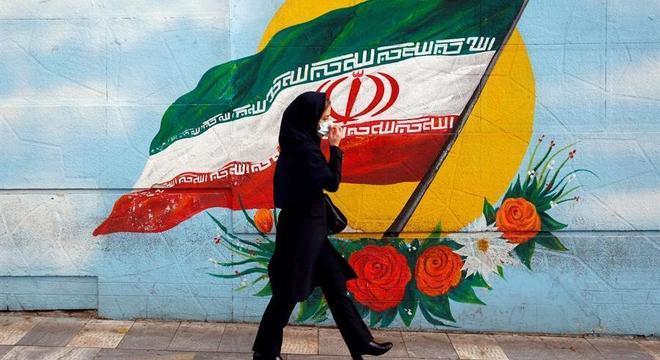 Mulher caminha diante mural com a bandeira iraniana em rua de Teerã