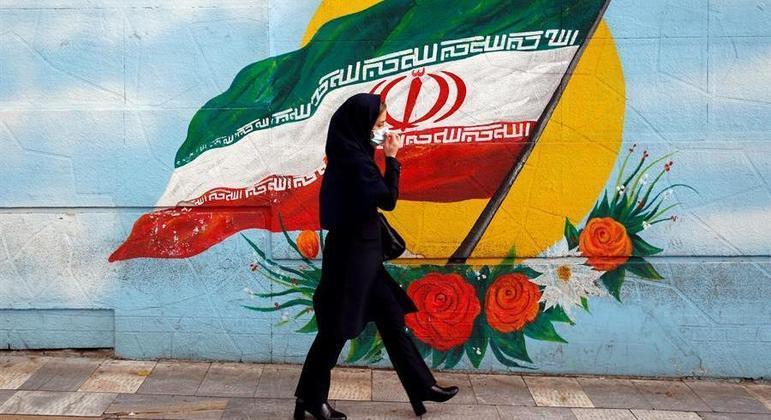 Mulher passeia ao lado de imagem da bandeira do Irã