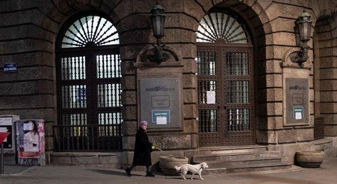 Mulher passeava com seu cachorro durante um toque de recolher imposto para impedir a propagação da doença por coronavírus em Belgrado.
