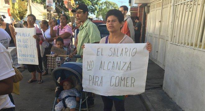 Mulher segura cartaz dizendo 'O salário não é suficiente para comer'