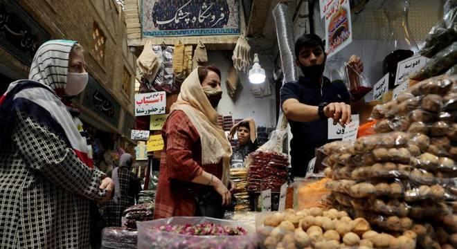 Mulher usa máscara enquanto vai a mercado em Teerã, capital do Irã