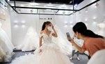 'Basicamente, não temos clientes', Zhu Yuan, presidente da Romen's Wedding Dress, falando de seu showroom, onde dezenas de vestidos de noiva enfeitados estavam amontoados uns contra os outros em prateleiras de roupas