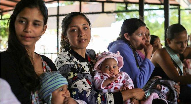 Celene Cacique (ao centro) diz que é difícil conseguir vacina na Venezuela. Do lado colombiano da fronteira, um posto de saúde oferece imunização gratuita aos bebês que chegam, mas a fila é grande