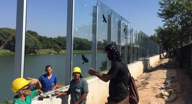 Funcionários trabalham na conclusão do muro de vidro