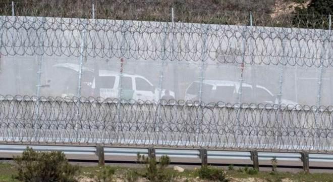 Agentes americanos perto de uma cerca dividindo a fronteira entre EUA e México em foto de dezembro de 2018
