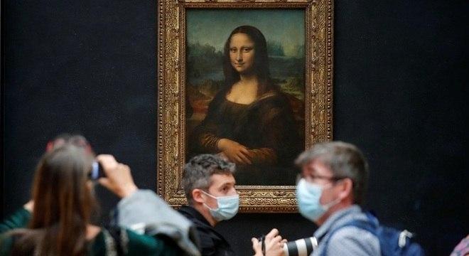Jornalistas em frente à obra Mona Lisa no Museu do Louvre