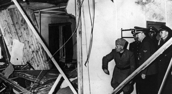 Mussolini e Hitler inspecionam os destroços da sala de conferências depois do ataque a bomba