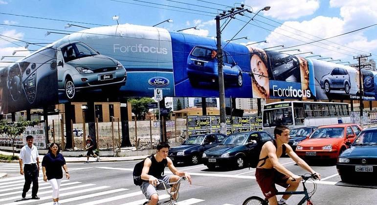 Ciclistas trafegam na esquina das avenidas Juscelino Kubitschek e Faria Lima em 16 de janeiro de 2001, ocupada por anúncio em terreno de 100 m por 80 m. Considerando a altura média de 3 m, o anúncio tinha área de 540 m.