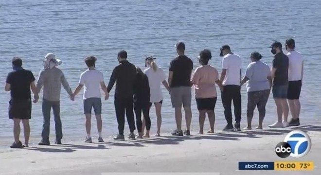 Grupo aparece de mãos dadas à beira do Lago Piru