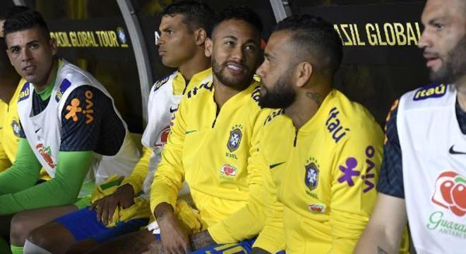 Neymar reserva, despreocupado com o jogo. Ao lado do parceiro Daniel Alves