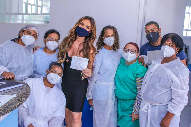 Nicole ainda posou com toda a equipe do posto de saúde, segurando seu cartão de vacinação