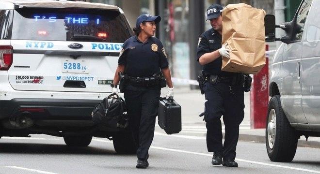 Policiais retiram um dos pacotes suspeitos encontrados perto de metrô em NY
