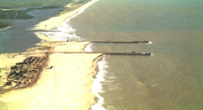 A construção de guias-correntes para manter aberto o Canal do Furado, no Rio de Janeiro, fez com que a areia se acumulasse de um lado e que do outro houvesse erosão