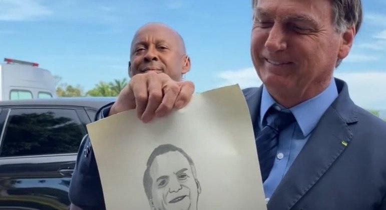 Bolsonaro segura um desenho em sua homenagem em encontro com apoiadores