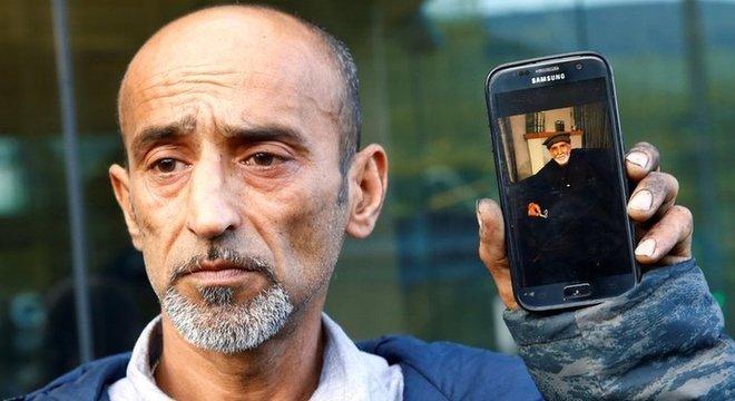 Omar Nabi mostra um celular com a foto de seu pai, Daoud, primeira vítima do ataque a ser identificada