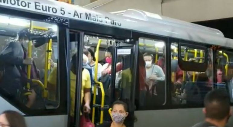 Passageiros desembarcam de ônibus lotado em terminal, sem respeitar o distanciamento