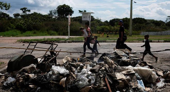 Venezuelanos caminham em frente a pertences destruídos após ataque de brasileiros em Pacaraima