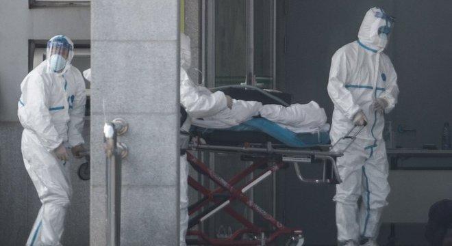 Paciente sendo levada a hospital em Wuhan; casos triplicaram em pouco tempo
