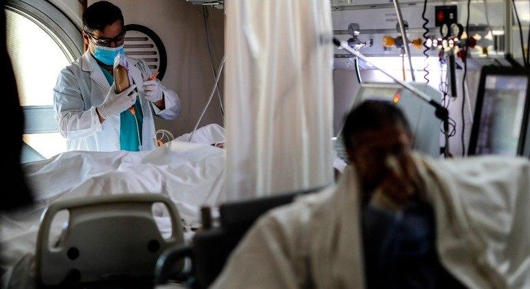 Um médico realizando o controle de seus pacientes na UTI de um hospital de Buenos Aires
