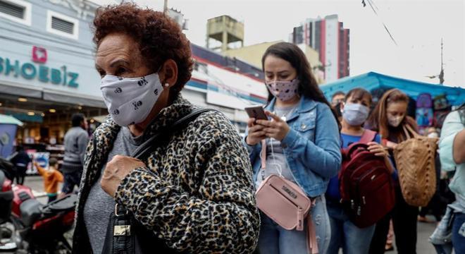 Pessoas com máscara fazem fila em comércio de São Paulo