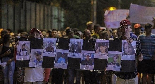 Manifestantes seguram cartazes com foto dos nove jovens mortos no baile
