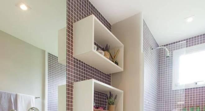 parede de pastilhas de vidro e nichos de madeira branca